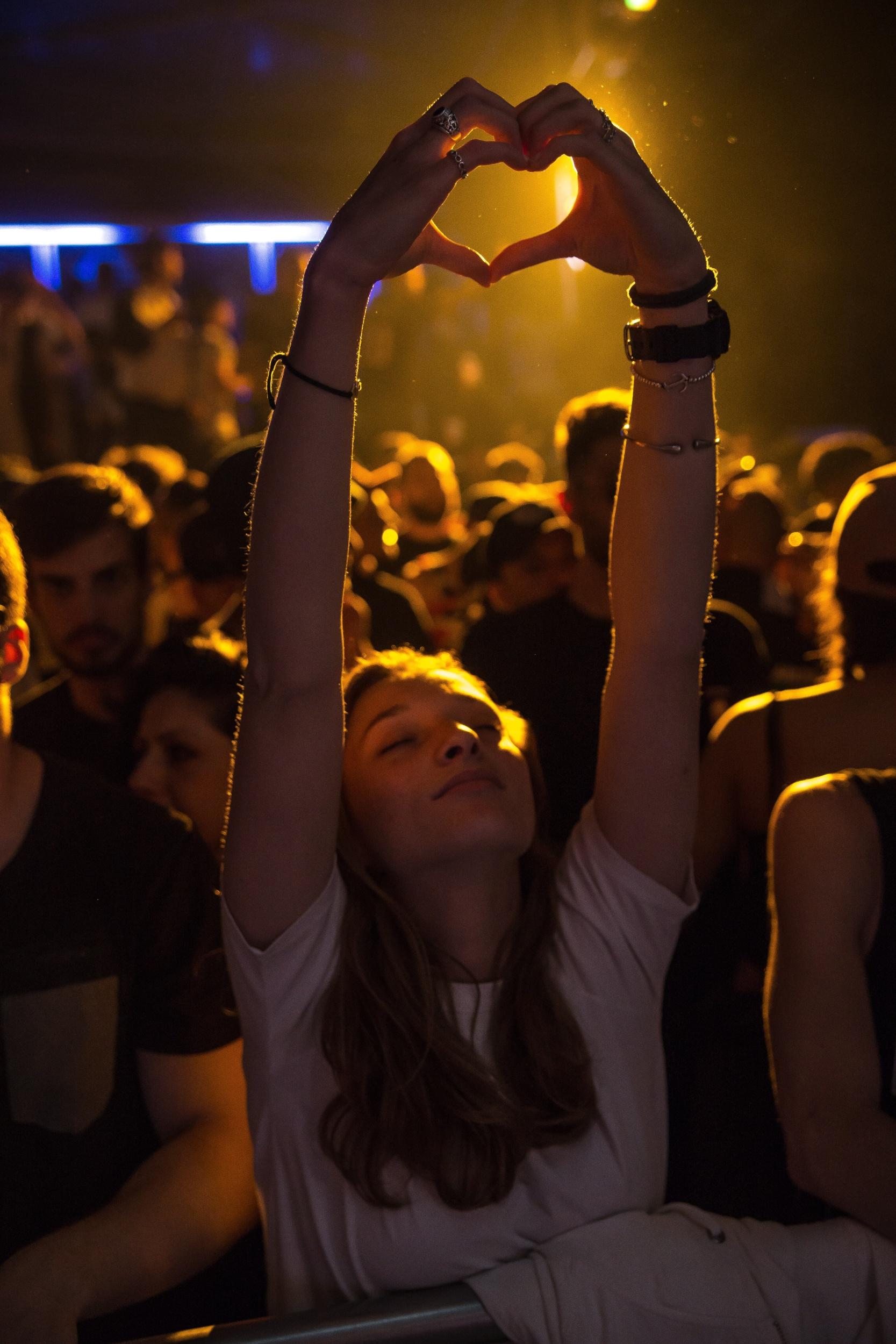Ein Teenager-Mädchen im Publikum auf einem Konzert ist von vorne zu sehen. Sie hält die Arme hoch und formt mit beiden Händen ein Herz. Von hinten strahlt ein gelebs Licht.