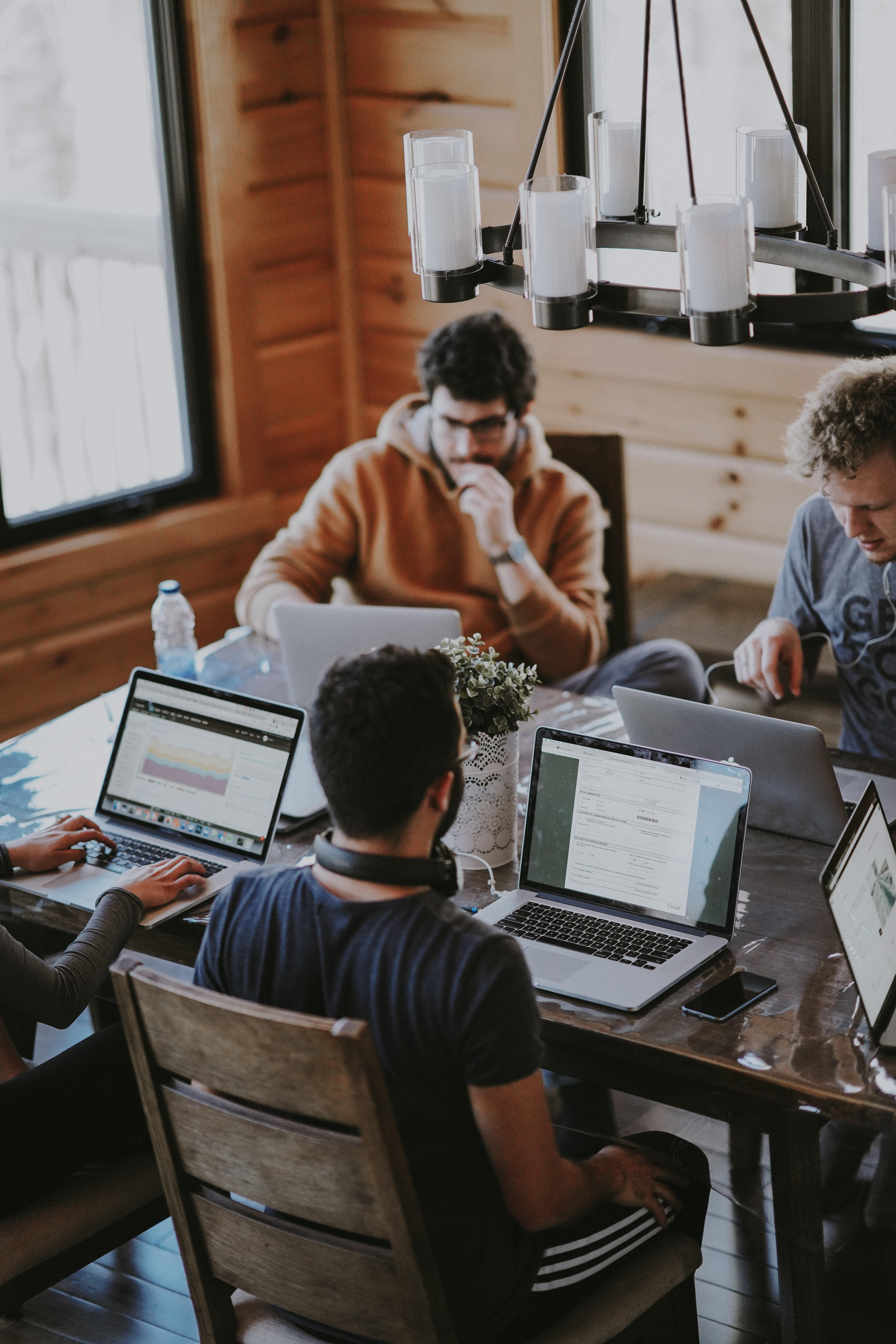 Foto: Vier junge Männder sitzen an einem Tisch und schauen in ihre Laptops, die vor ihnen stehen.