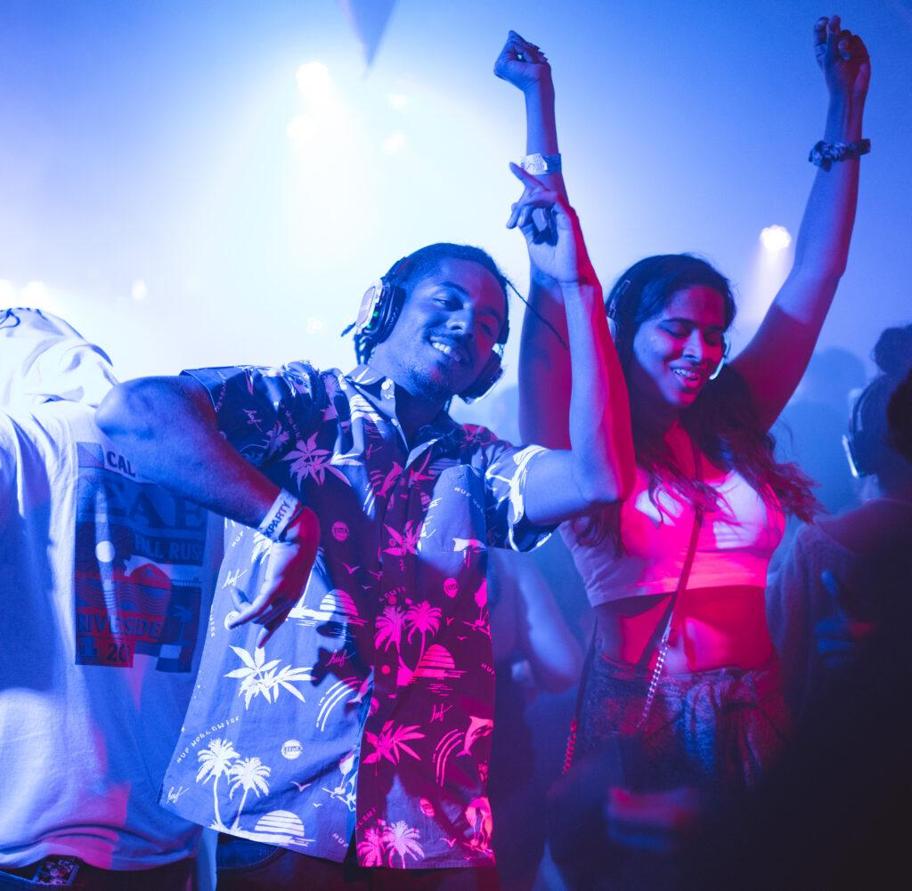 Foto: Ein junger Mann und eine junge Frau, beide ungefähr 20 Jahre alt, stehen in einer Menge und haben Kopfhörer auf und tanzen mit den Händen in der Luft.