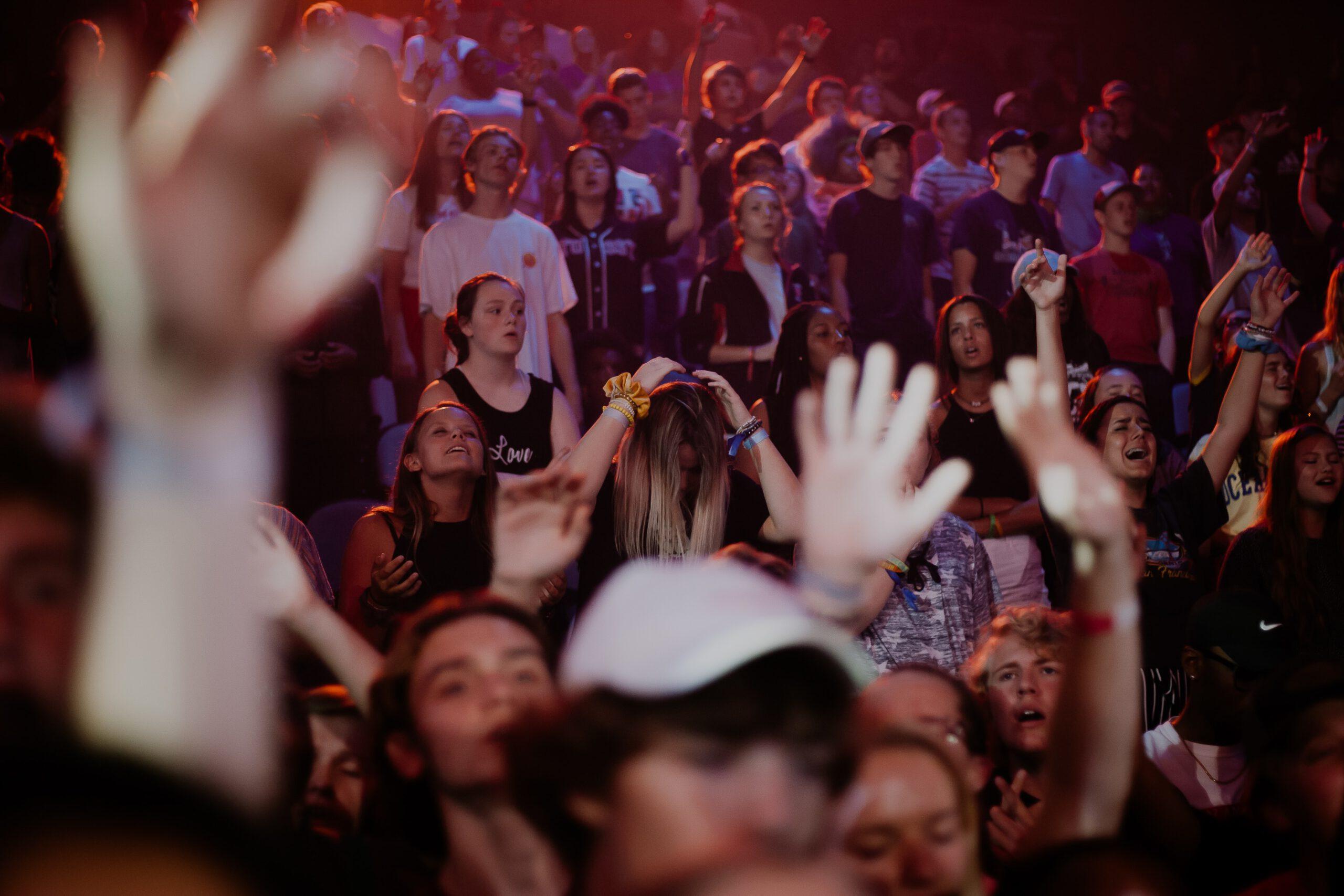 Viele Menschen Im Publikum, Die Zum Teil Die Arme Hochstrecken Und Lachen