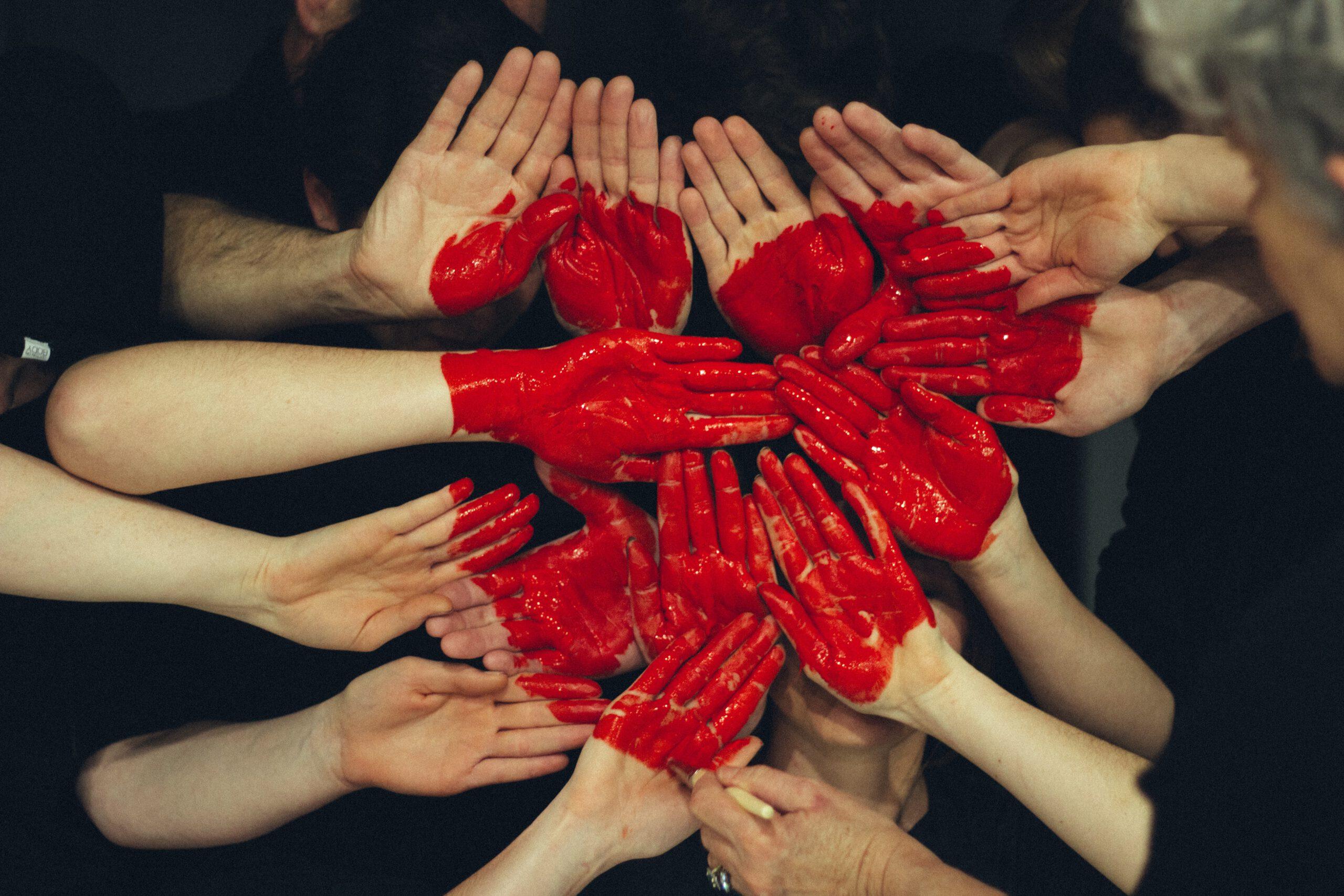 18 Arme Aus Der Vogelperspektive , Die Sich In Form Eines Kreises An Der Spitze Ihrer Hände Berühren. Über Alle Hände Ist Mit Roter Farbe Ein Großes Herz Gemalt.