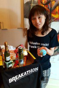 Ein Foto einer Helferin und dem geöffneten Paket, in dem sich eine Piccolo Sekt, After Eight Schokolade, Chips, eine Dose Mate und Red Bull und ein T-Shirt vom Breakathon befindet